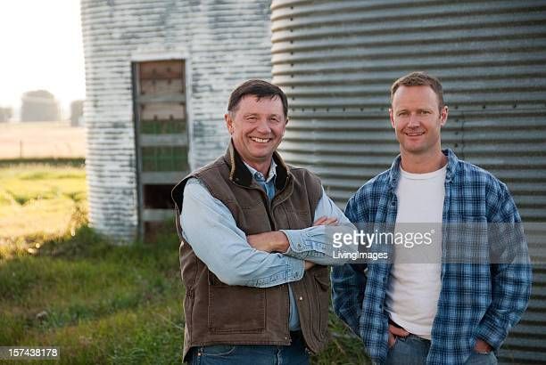 A father and son posing for a photo at a family farm