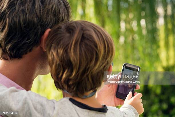 Father and son posing for photograph with smartphone