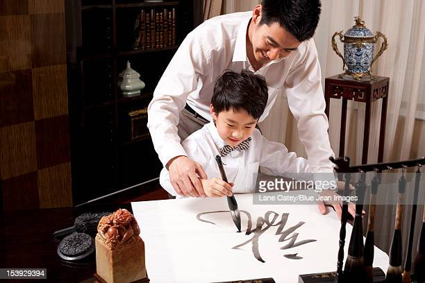 Father and son practising Chinese calligraphy