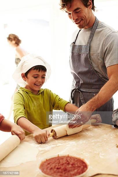 A father and son prepare pizza.