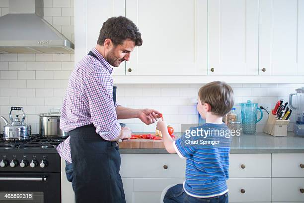 Father and son preparing food at home