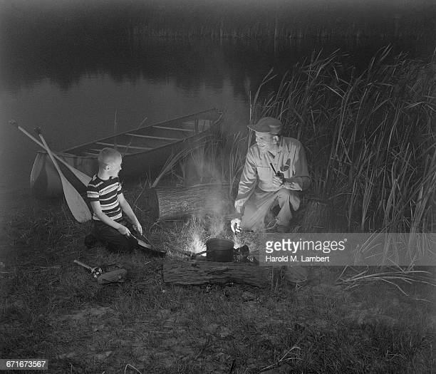 father and son preparing food on camp stove - historisch stock-fotos und bilder