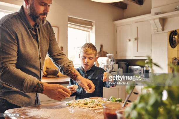 father and son preparing pizza in kitchen - dean foods stock photos and pictures