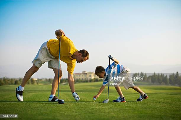 Father and Son Preparing to Tee Off