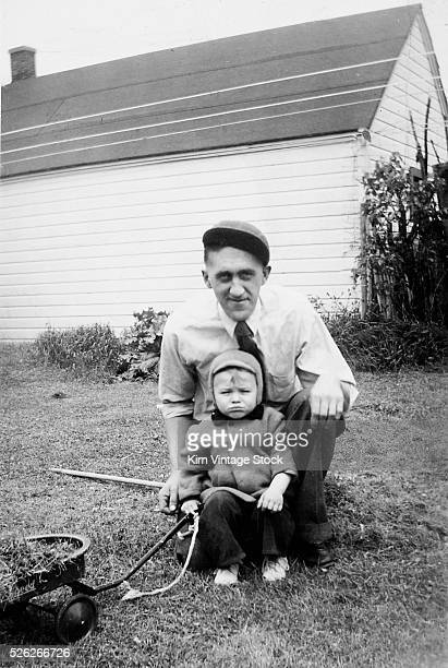 Father and son pull a wagon in backyard ca 1946