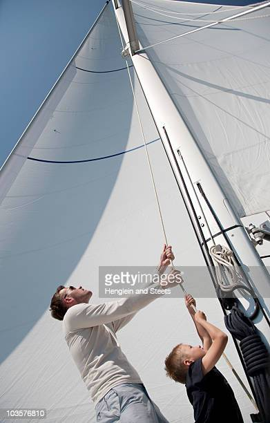 Father and son pulling rope on yacht