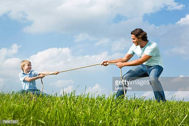 Father and son (6-7) pulling rope in meadow
