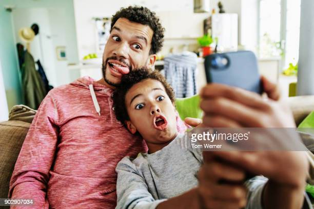 father and son pulling silly faces while taking selfie together - self portrait stock pictures, royalty-free photos & images