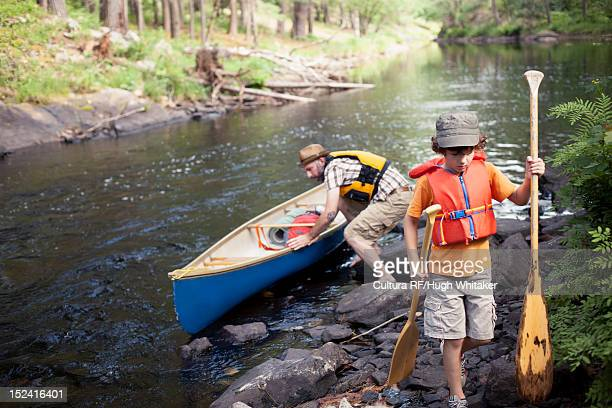 Father and son pushing canoe in river