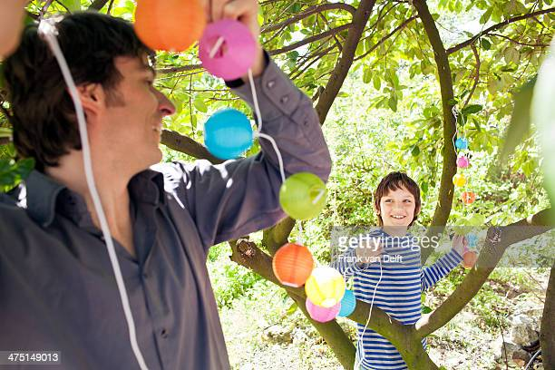 Father and son putting fairy lights in tree