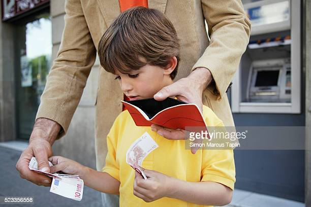 Father and Son Putting Money in Wallet