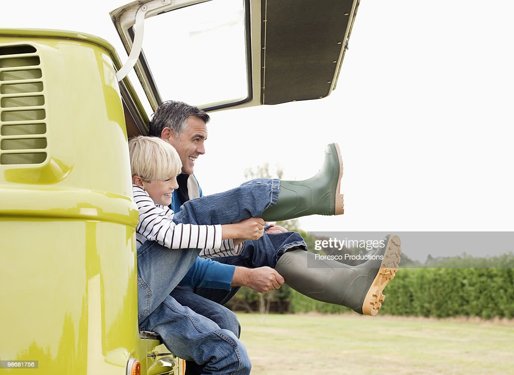 Father and son putting on boots : Stock-Foto