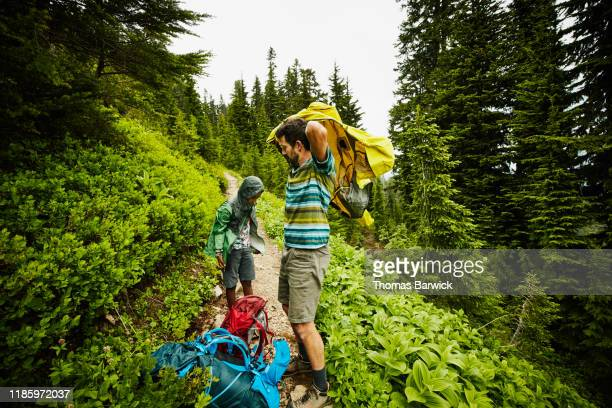 Father and son putting on rain jackets while hiking on alpine trail