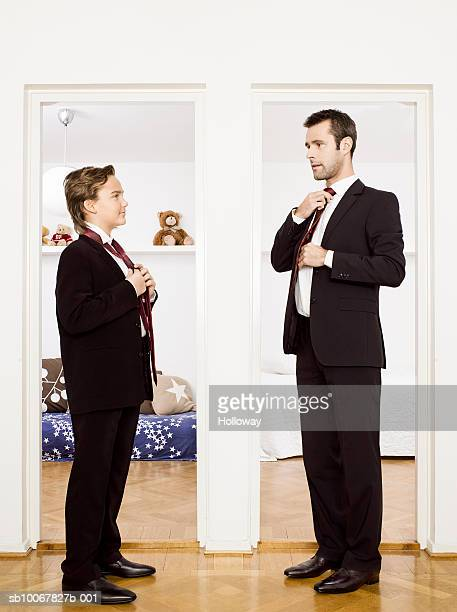 Father and son (10-11) putting on ties, standing face to face at home, side view