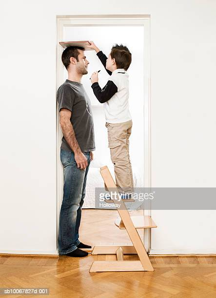 Father and son (10-11years) putting on ties, standing face to face at home, side view