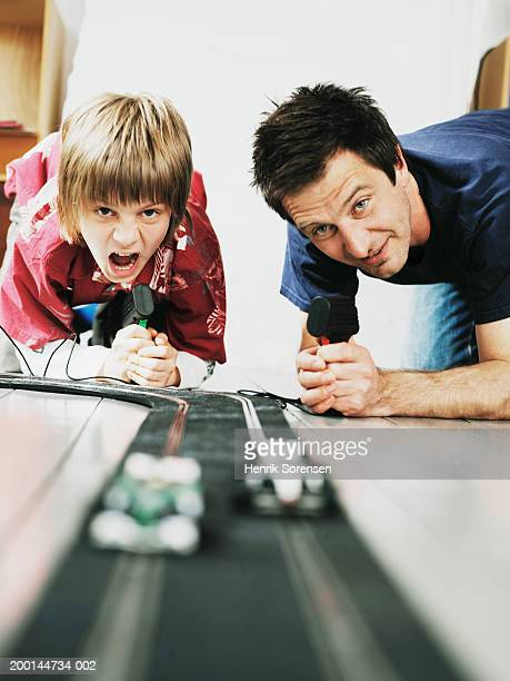 Father and son (9-11) racing toy cars, ground view