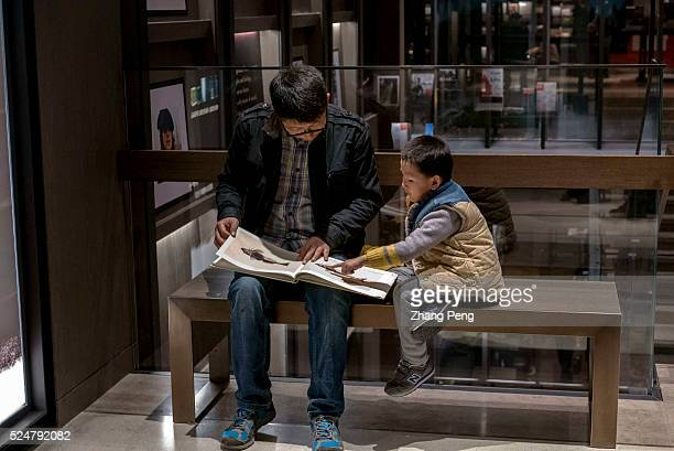 A father and son read picture book in the Suzhou Eslite Bookstore Eslite Bookstore is the largest retail bookstore chains originated in Taiwan and...