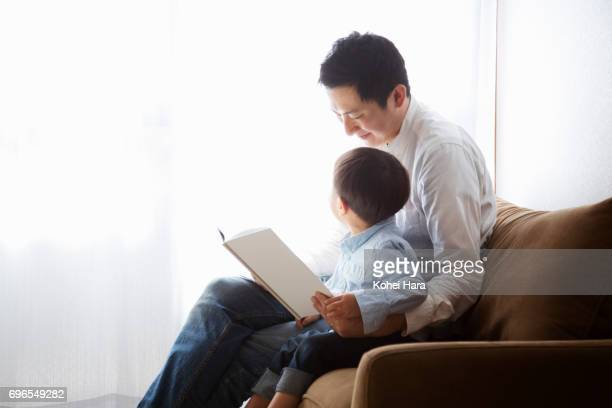 Father and son reading a book together
