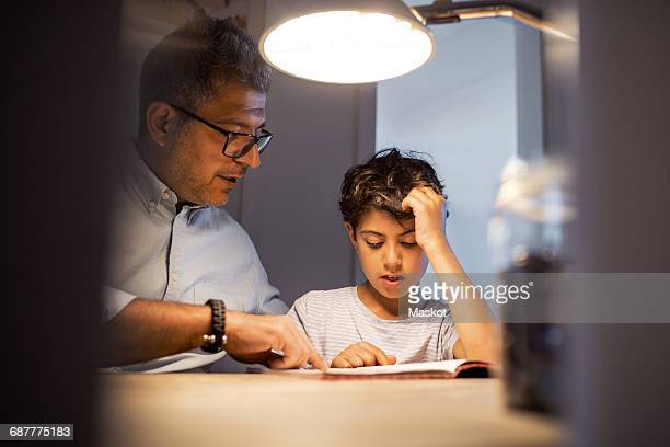Father and son reading book in darkroom at home