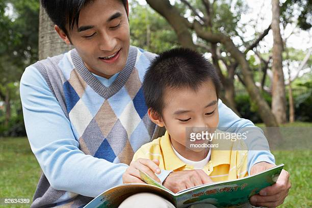 Father and son (7-9) reading book in park