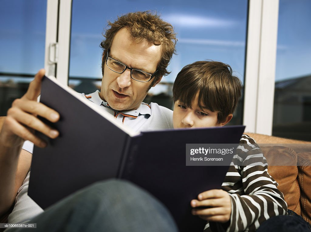 Father and son (8-9) reading book on sofa : Foto stock