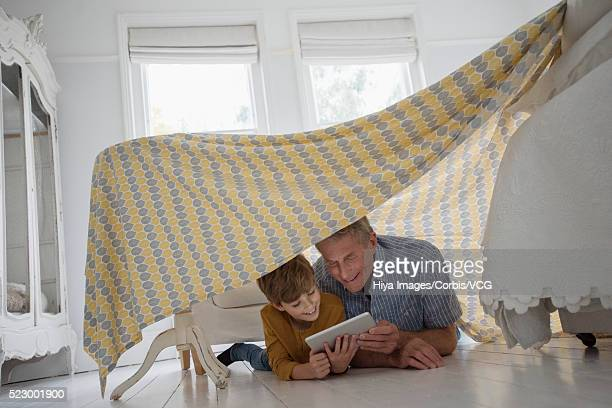 Father and son reading in blanket fort