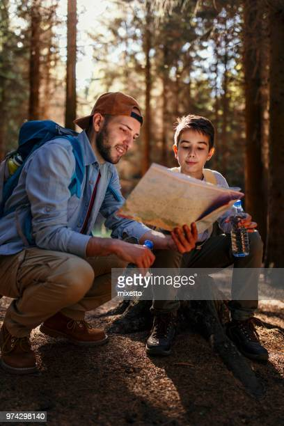 Father and son reading man in forest
