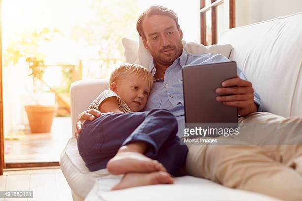Father and son reading on digital tablet