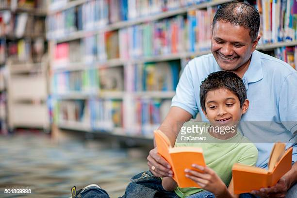 Father and Son Reading Together in the Library