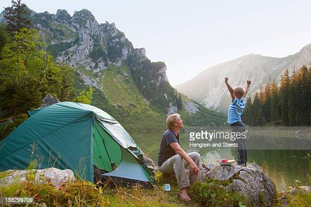 father and son relaxing at campsite - camping stock photos and pictures