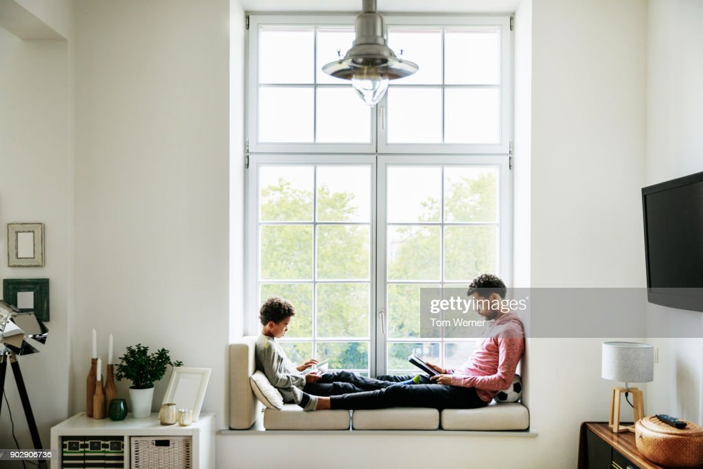 Father And Son Relaxing By Large Window At Home : Stock Photo
