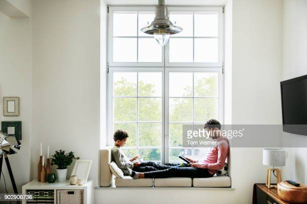 father and son relaxing by large window at home - huiselijk leven stockfoto's en -beelden