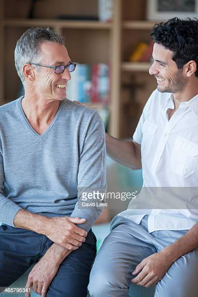 Father and son relaxing in living room