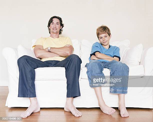 Father and son (9-11) relaxing on sofa, arms crossed, portrait