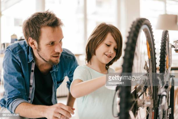 father and son repairing bicycle together at home - familia con un hijo fotografías e imágenes de stock