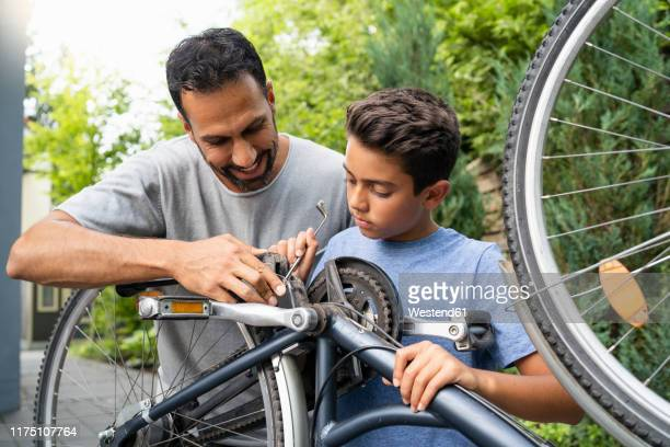 father and son repairing bicycle together - männer über 30 stock-fotos und bilder