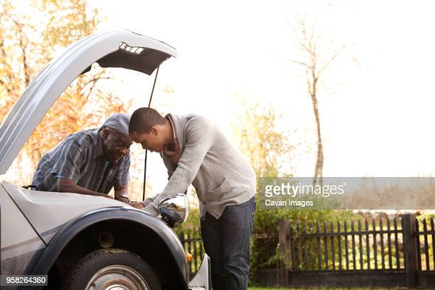 Father and son repairing car against sky