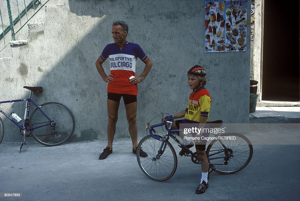 A father and son resting after an amateur bicycle race in Carrara, Italy, circa 1980.