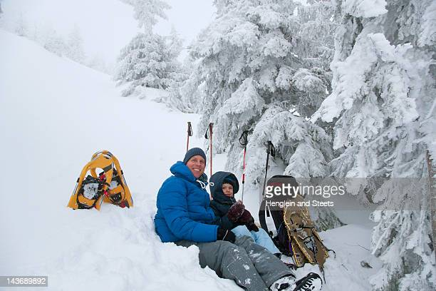 Father and son resting while snowshoeing