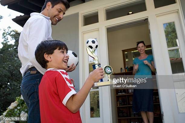 Father and son (6-8) returning home, boy holding  soccer trophy