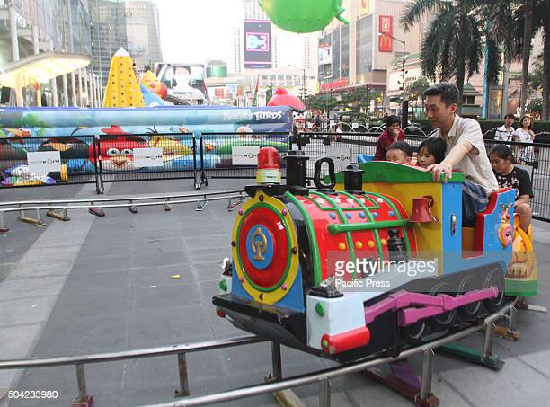 Father and son ride on a toy train during the National Children's Day at the front of Central World