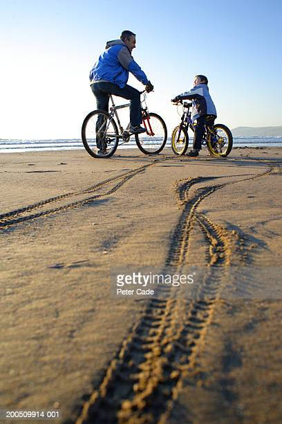 Father and son (6-8) riding bicycles on beach, tracks in foreground