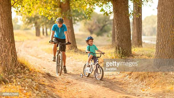 father and son riding bicycles - cycling helmet stock photos and pictures