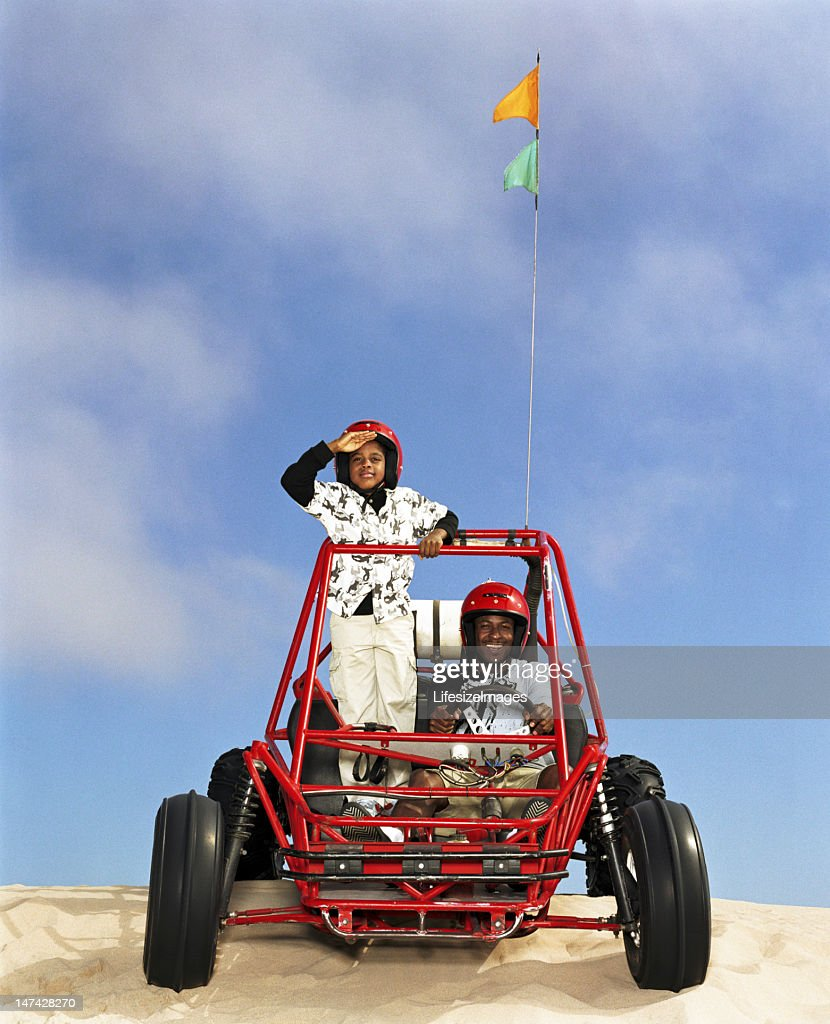 Father and son (8-10) riding in dune buggy : Stock Photo