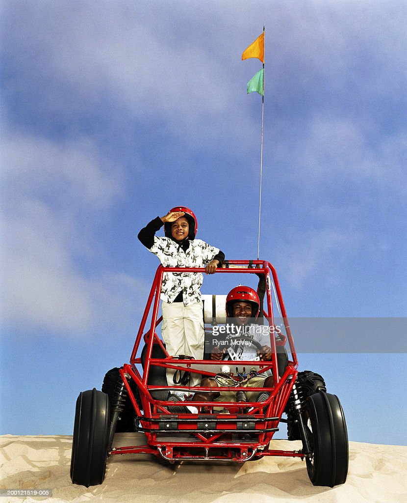 Father and son (8-10) riding in dune buggy : Foto de stock