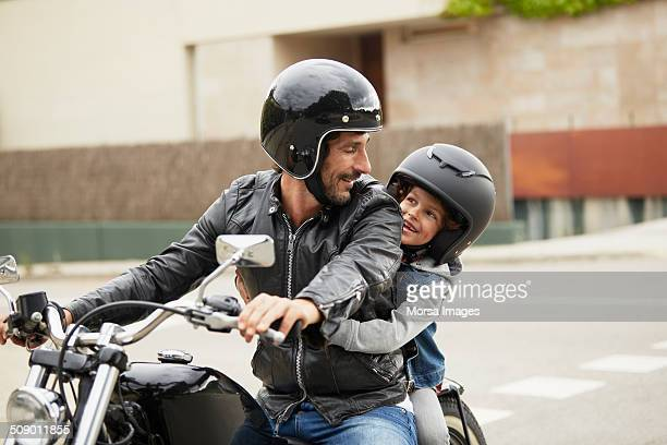father and son riding motorbike - vertrauen stock-fotos und bilder