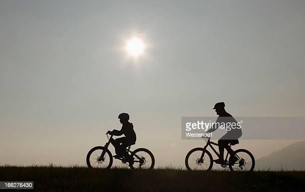 father and son (10-11) riding mountain bikes, silhouette - montar fotografías e imágenes de stock