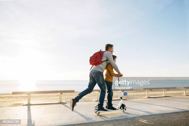 father and son riding scooter on beach promenade at sunset - scooter stock pictures, royalty-free photos & images