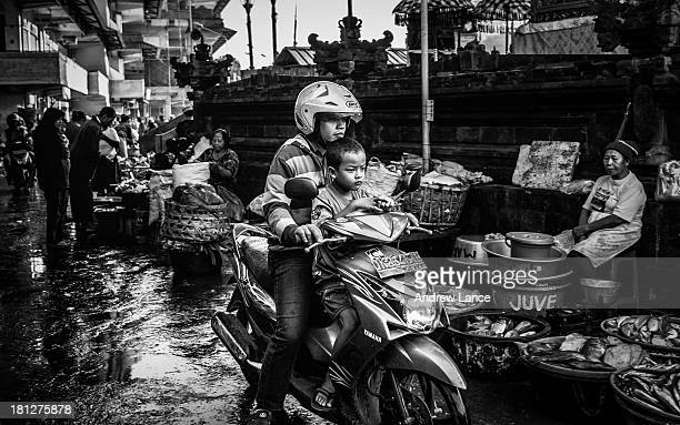 Father and son riding together on a scooter, navigate through the busy Pasar Badung markets, Denpasar, Bail, Indonesia. Photo processed in black and...