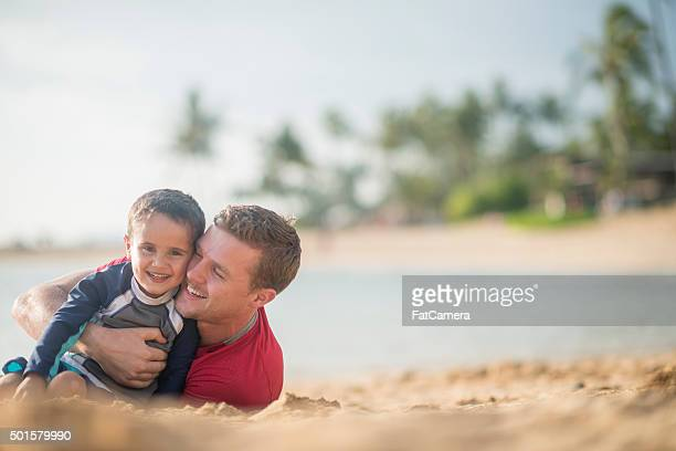 Father and Son Rolling in the Sand